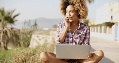 Young African Woman Working On Laptop In Nature.