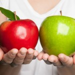 Comparison. Hands holding red and green apples